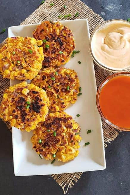Delicious corn cakes served on the white serving platter.
