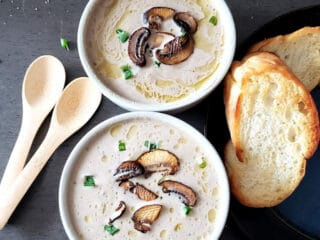 Creamy Mushroom Soup served in two soup bowls. There is toasted bread and wooden spoons on the side. This vegan and gluten free soup is homemade.