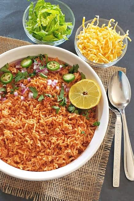 A white serving bowl full of colorful Spanish/ Mexican rice