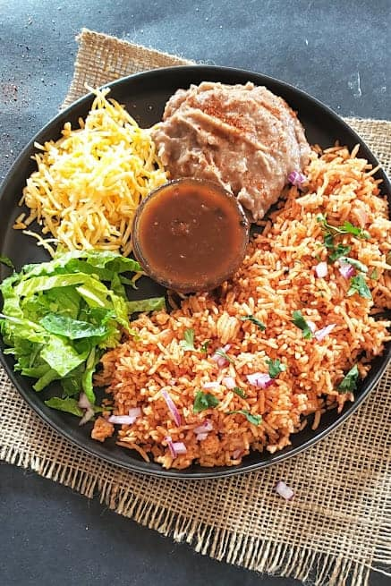 Mexican Spaish rice served with refried beans, salsa, cheese and lettuce for the dinner.