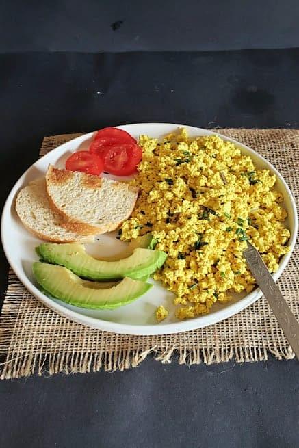 A breakfast platter full of scrambled tofu, toast, avocado and cut tomatoes.