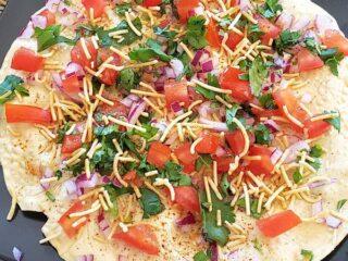 Close up showing beautifully layered vegetarian Indian masala papad.
