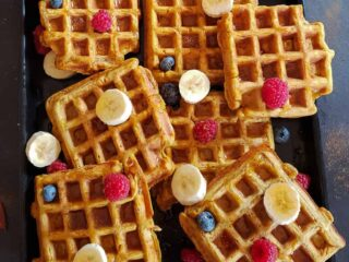 A tray full of vegan and gluten free pumpkin waffles served with fresh berries and maple syrup.