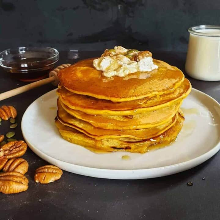 Stack of healthy vegan pumpkin pancakes served with coconut cream, maple syrup and pecans.