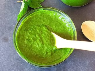 Thick green mint cilantro Indian Chutney served in a glass bowl with wooden spoon.