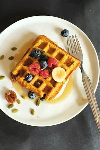 A white snack plate with pumpkin waffle, maple syrup and cut up fruit.