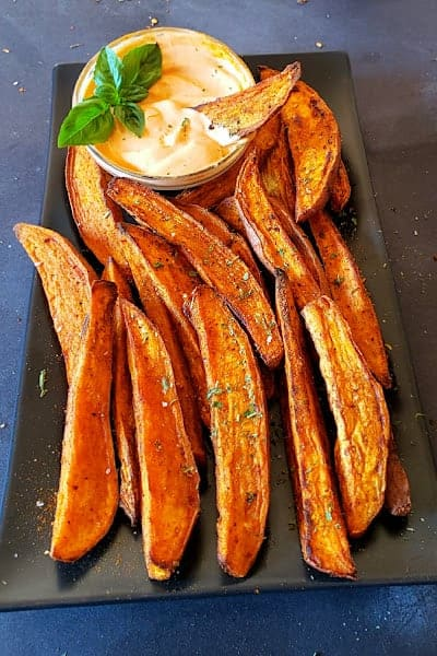 Air fryer sweet potato wedges served on black serving plate with garnishes.