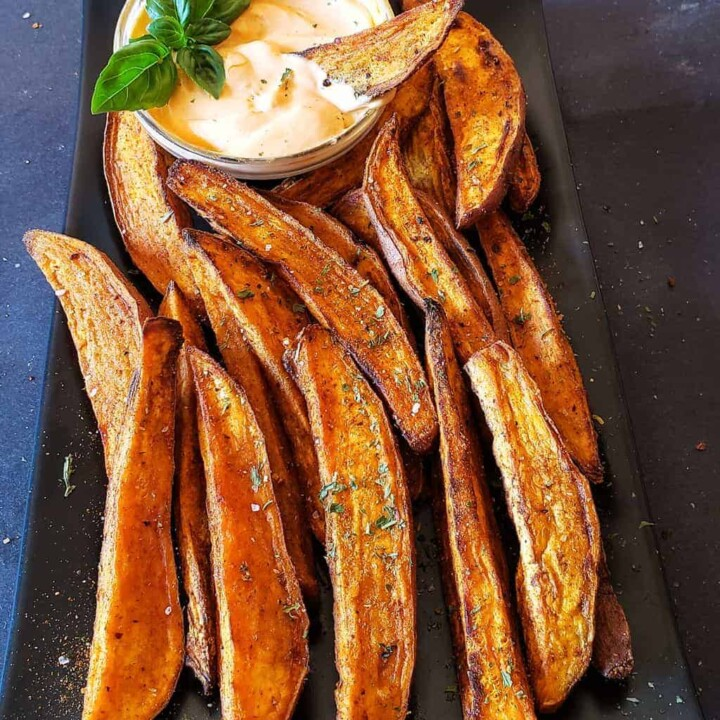 Air fryer sweet potato wedges served with spicy dip.