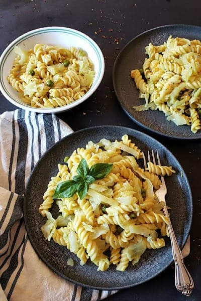A dinner serving with three plates of cabbage pasta with garnishes.