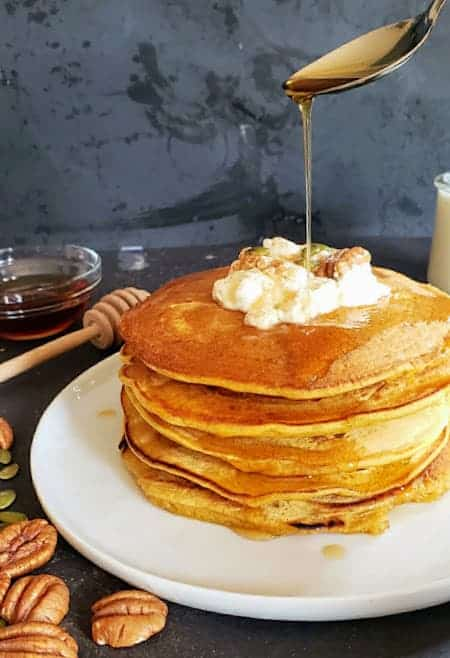 Maple syrup being poured on stack of homemade pumpkin pancakes.
